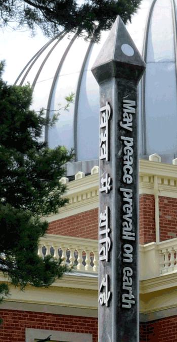 Stainless steel peace pole with raised text created by sculptor Joel Selmeier