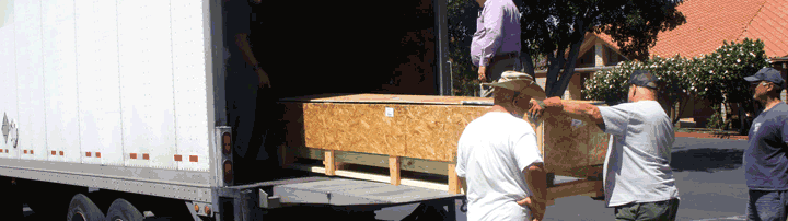Sliding a stone peace pole crate onto the lift gate for unloading from a semi truck.