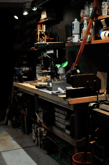 The workbench in my shop with a manual metal shear and a  massive vice and a drill press below shelves of supplies